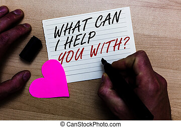 Handwriting text writing What Can I Help You With question. Concept meaning Offering assistance Experts advice ideas Written on notepad hand hold marker with love heart wooden background.