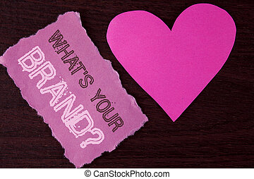 Handwriting text writing What is Your Brand Question. Concept meaning asking about your company manufacturer or model written on Tear Sticky Note Paper Piece on wooden background Heart next to it.