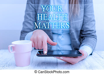 Handwriting text writing Your Health Matters. Concept meaning good health is most important among other things Business woman sitting with mobile phone and cup of coffee on the table.
