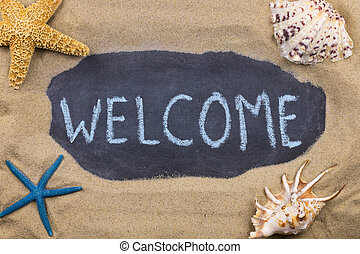 Handwritten chalk inscription WELCOME on blackboard, lying among the seashells and starfish on the sand.