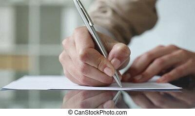 Handwritten document - Close-up of a female worker writing a...