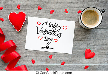 Handwritten greeting card with text Happy Valentines day on wooden background with red hearts, ribbon and coffee cup