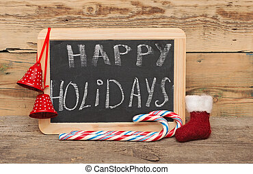 Handwritten happy holidays greeting on a small chalkboard with candy canes, red bell and small Santa boot