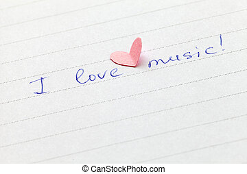 """Handwritten phrase """"I love music"""" with heart. Shallow depth of field."""