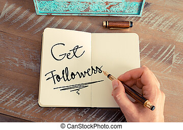 Retro effect and toned image of a woman hand writing a note with a fountain pen on a notebook. Motivational concept with handwritten text GET FOLLOWERS