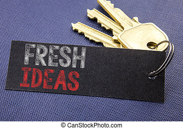 Handwritten text showing Fresh Ideas. Business concept writing for Thinking Inspiration Inspire Creativity Written on note paper attached to the key, black background with space close up