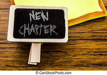 Handwritten text showing New Chapter. Business concept for Starting New Future Life written on announcement board on the wooden wood background.