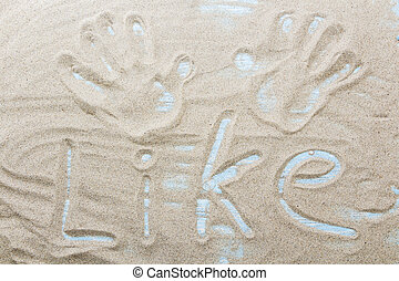 Handwritten word LIKE on brown sand on the beach in sunny day.