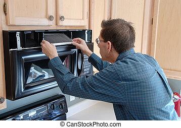 Handy Man Home Repair - Man replacing the filter in a...