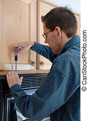 Man using a screwdriver to repair his microwave in the kitchen of a modern home.