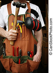 Handy man in front of workshop loaded with tools