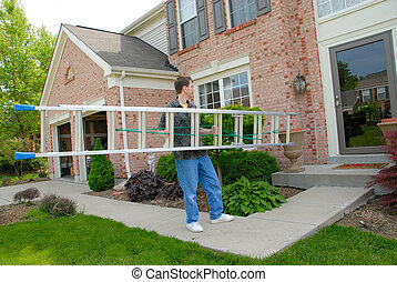 a man carrying an aluminum ladder toward the front door of a brick house in the springtime