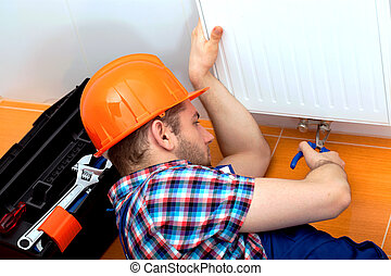 Handy man repairing heater - Handy man in a hard hat...