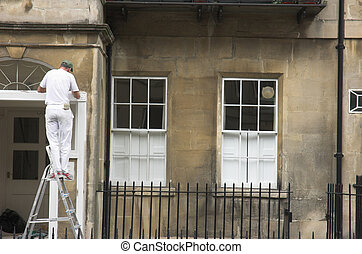 Handyman - A painter works on property exterior.
