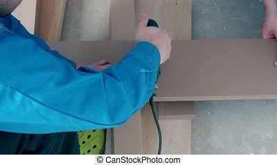 Handyman adapting laminate wooden floor board to fit on flooring
