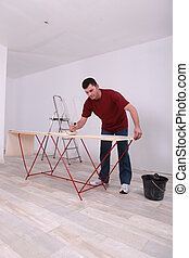 Handyman applying glue on wallpaper
