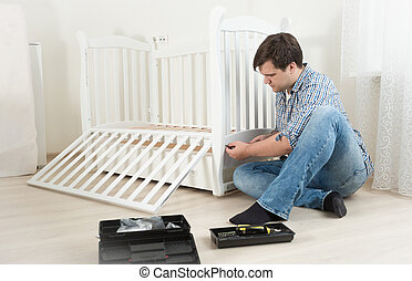 Handyman assembling wooden furniture in children's room