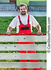 Handyman building a wooden fence