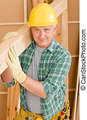 Handyman carpenter mature carry wooden beam