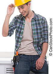 Handyman. Cheerful craftsperson adjusting his hardhat and smiling