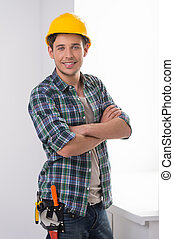 Handyman. Cheerful craftsperson looking at camera and keeping arms crossed