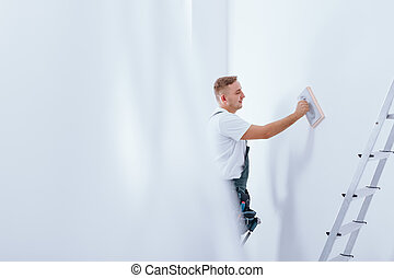 Handyman cleaning white wall