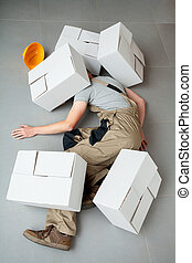 Handyman crushed by cartons - Unconscious handyman lying...