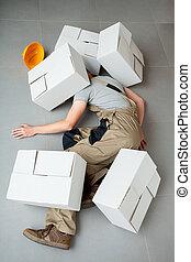 Handyman crushed by cartons - Unconscious handyman lying...