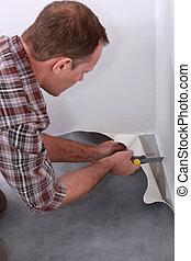 Handyman cutting linoleum flooring to fit a corner of a room