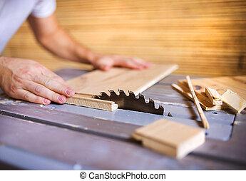 Handyman cutting plywood on circular saw - Unrecognizable...