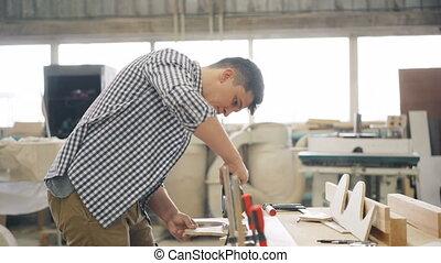 Handyman cutting wood with fretsaw using electric instrument...