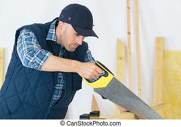 handyman cutting wood with hand saw