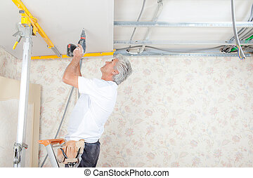 Handyman drilling into the ceiling