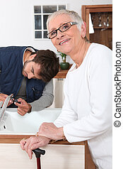 Handyman fixing a kitchen tap for a senior woman