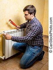 handyman fixing heating radiator with red plumber pliers