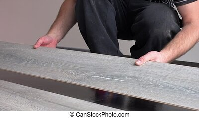 handyman guy take laminate board and install it on floor....