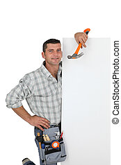 Handyman holding a hammer and a blank sign