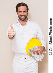Handyman holding his yellow helmet showing thumbs up
