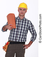 Handyman holding roof tiles