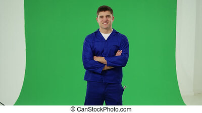 Handyman in blue overalls - Front view of a young Caucasian ...