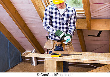 Handyman in yellow safety helmet with a tool belt.