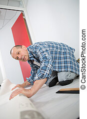 handyman installing new layered wooden parquet