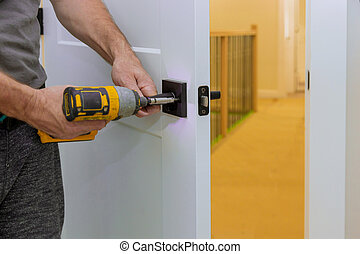 Handyman installing the door lock in the room with screwdriver, Close-up of new a house