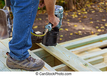 Handyman installing wooden flooring in patio, working using nail gun to nail