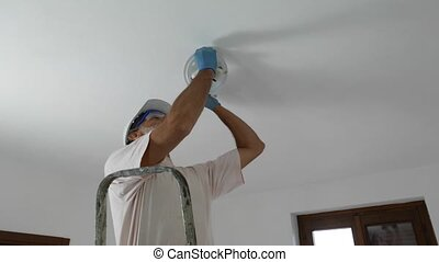 Handyman lamp mount - Man installing a lamp on the ceiling