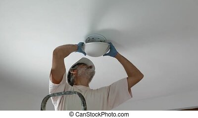 Man installing a lamp on the ceiling