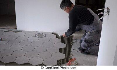 Handyman lay hexagon tiles on floor in new apartment under...
