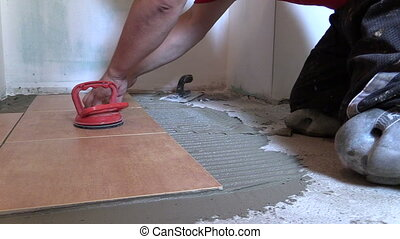 handyman lay tiles - Handyman worker place floor tiles. Home...