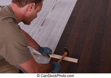 handyman laying floorboards