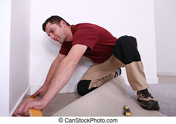 handyman laying wall-to-wall carpet
